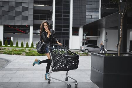 Brunette model in a leather jacket and shorts is standing with a shopping trolley and posing on the street near the modern building of hypermarket. Stock Photo