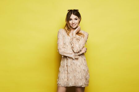 A beautiful smiling model girl with tender makeup, in sunglasses and cocktail dress, posing over yellow background, isolated. Concept of teenage fashion