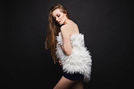 A beautiful young woman, in a blue cocktail dress and in modish cape from artificial fur, posing at the black background, isolated. A stylish model girl in fashionable white fur cape Stock Photo