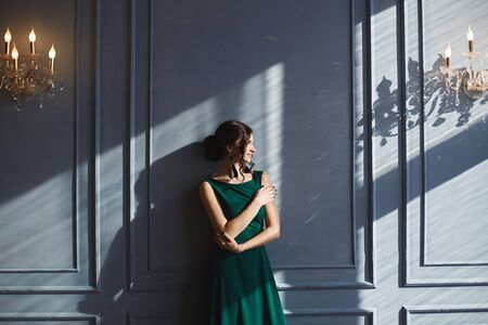 A beautiful brunette girl with modish hairstyle, in green evening dress, stands at the blue wall with sunlight and shadows. A young woman in a modish outfit enjoys a sunny day in vintage interior. Stock Photo