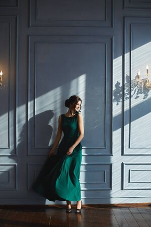 A beautiful brunette girl with modish hairstyle, in green evening dress, dancing near the blue wall with sunlight and shadows. A young woman in a modish outfit enjoys a sunny day in vintage interior. Stock Photo