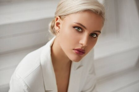 A fashionable young woman with perfect blond hair and perfect trendy makeup in an elegant white suit posing in studio. Beautiful blonde model girl with red full lips and deep seductive eyes.