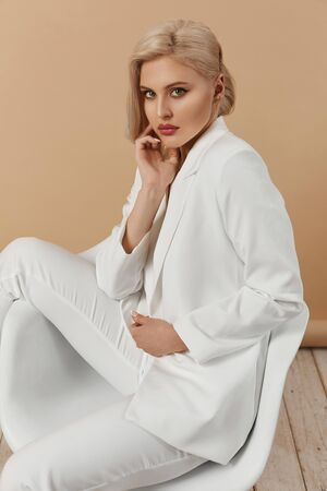 A fashionable young seductive woman with perfect body and with perfect blond hair in an elegant white suit posing in studio. Beautiful blonde model girl with full lips and trendy makeup.
