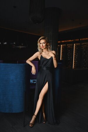 A beautiful blonde leggy woman with a perfect body in black evening dress posing in the interior of a luxurious restaurant. Modish model girl in bright evening makeup. Concept of high fashion.