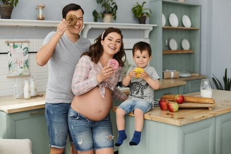 Happy young family, a beautiful pregnant woman with her handsome man and baby boy making breakfast and eating tasty donuts at the kitchen in the morning. Concept of happy family.