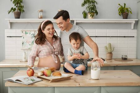 Happy young family, a beautiful pregnant woman with her handsome man and baby boy making breakfast at the kitchen in the morning. Concept of the happy family.