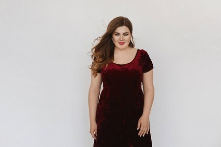 Beautiful plus size model girl in modish red velvet dress isolated at white background. Young fat woman with bright makeup and with stylish hairstyle posing in studio. Concept of XXXL fashion. Stock Photo