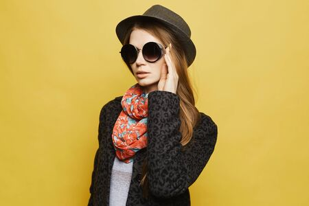 A beautiful young woman in modish coat, trendy hat and sunglasses posing at the yellow background, isolated. Model girl with blond hair in modish autumn outfit. Concept of street fashion