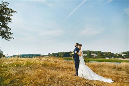 Beautiful bride hugging groom tenderly in a wheat field somewhere in the countryside. Young woman in a white wedding dress and brutal handsome man in a blue business suit posing outdoors. Loving couple gets married in the summer in the field. The concept of happiness, love, new life.
