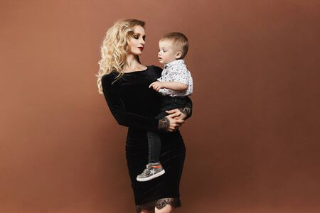 Beautiful and happy young blonde woman in a black dress with a cute little baby boy on her hands, isolated at background. Concept of modern maternity.
