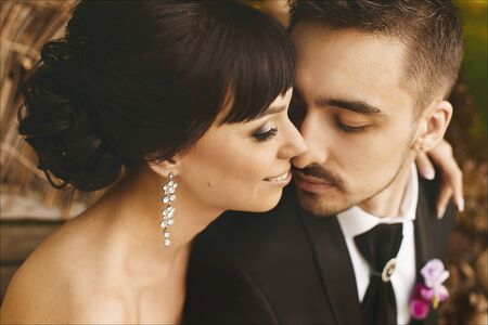 Beautiful and happy couple of just married hugging and kissing, a handsome young man in a stylish black suit and young brunette model woman with wedding hairstyle in a lace dress.