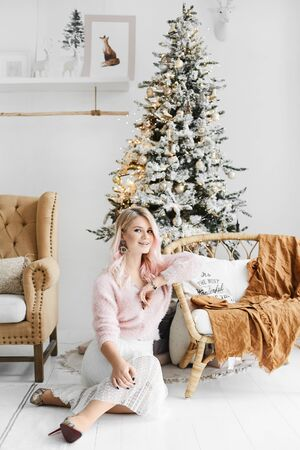 Young blonde beauty in white sweater and lace skirt sits on the floor near the Christmas tree. Stylish model girl in modish outfit posing in the interior decorated for New year.
