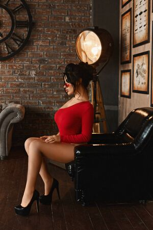Side view of a young brunette woman, with a sexy body and a big bust, in red bodysuits and high heels sitting in a leather armchair. Sensual busty model girl in a red modish outfit.