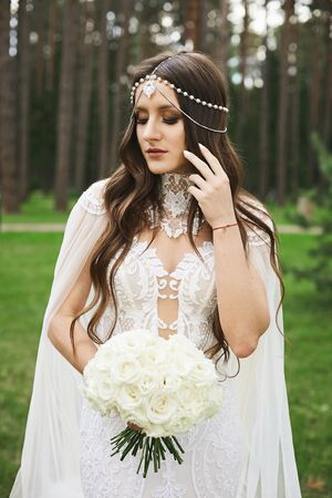 Stylish model girl with jewelry in her wedding hairstyle and bright makeup wearing in lace wedding dress keeping a bouquet and posing in green park