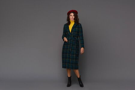 Young beautiful fashionable woman in trendy autumn coat, red beret and yellow sweater isolated at the grey background. Copy space for text.