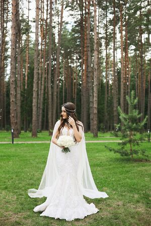 Young stylish woman with jewelry in her hairstyle wearing in lace wedding dress keeping a bouquet of flowers and posing in the forest. Beautiful model girl in wedding outfit posing outdoors.