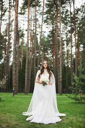 Young stylish bride with jewelry in her hairstyle wearing in lace wedding dress keeping a bouquet of flowers and posing in the forest. Beautiful woman in wedding outfit posing outdoors.