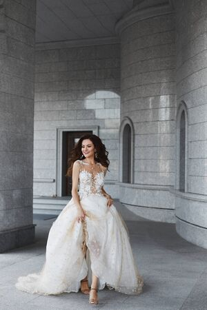 A happy model woman with a wedding hairstyle in a white lace dress runs through the courtyard of an ancient church. Beautiful young bride holds her wedding dress in her hands and poses in the old city Stock Photo