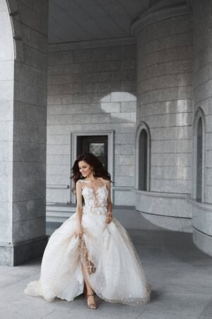 A happy young bride with a wedding hairstyle in a white lace dress runs through the courtyard of an ancient church. Beautiful model girl holds her wedding dress in her hands and poses in the old city