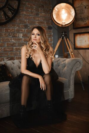 Gorgeous young model woman with smoky eyes in a beautiful black dress with tulle skirt sits on a couch in loft interior. Fashionable girl in modish outfit posing in interior Stock Photo