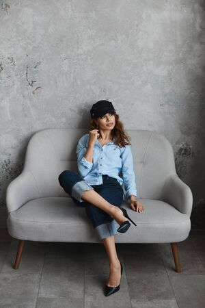 High fashioned model girl wearing high heel shoes, hat, blue shirt and roll-up jeans. Beautiful young woman in modish outfit sits on the couch and posing in the interior. Concept of street fashion.