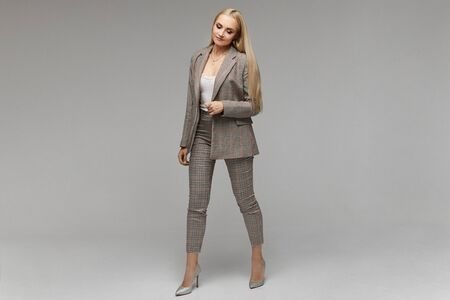 Smiling young elegant businesswoman with bright makeup and in suit looking down in the studio, isolated on grey background. Model girl in the business outfit, portrait in full length with copy space.
