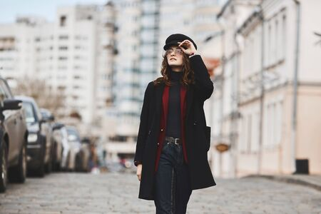 Charming young woman in a winter coat, modish hat, and sunglasses, walking down the street in a big city. Concept of street fashion.