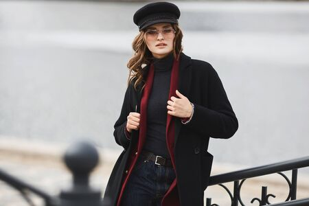 Fashionable young woman in a coat, modish hat, and sunglasses posing over an urban background. Beautiful model girl in modish outfit Concept of street fashion. Copy space.