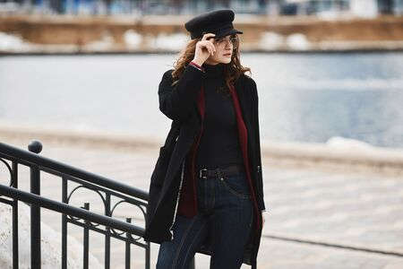 Fashionable model girl in a coat, modish hat, and sunglasses posing over an urban background. Beautiful young woman in modish outfit Concept of street fashion. Copy space.