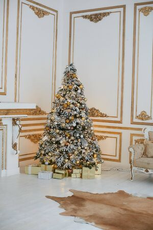 Beautiful decorated golden Christmas tree with present boxes under it in vintage luxurious interior decorated for New year. Concept of Christmas eve. Concept of New year party Stock Photo