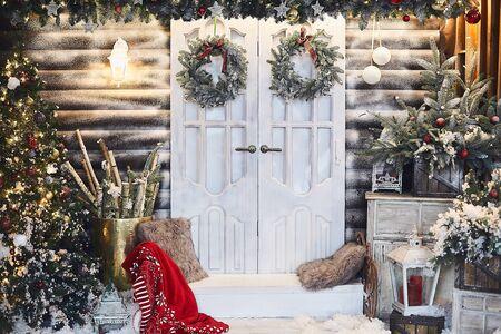 Rustikales Interieur des Winters verziert für das neue Jahr mit Kunstschnee und Weihnachtsbaum. Winterfassade eines Landhauses mit Weihnachtsdekoration im rustikalen Stil. Heiligabend. Standard-Bild