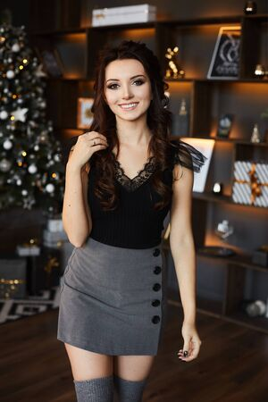 Beautiful brunette model girl with bright makeup in grey mini skirt, stockings and black blouse holding hand near the shoulder and posing near the Christmas tree at interior decorated for New Year.