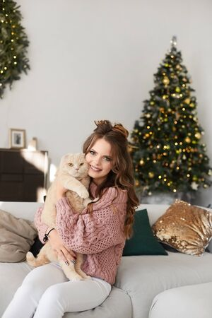 Fashionable happy model girl in cozy sweater holding the cat in the living room with Christmas tree and festive lights on the background. Young woman in winter outfit hugging a cute kitty and smiling