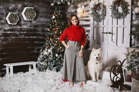 Happy model girl in a red cozy sweater and checkered pants posing with cute snow white Samoyed dog at Christmas rustic interior. Beautiful young woman in modish outfit posing with a cute fluffy dog