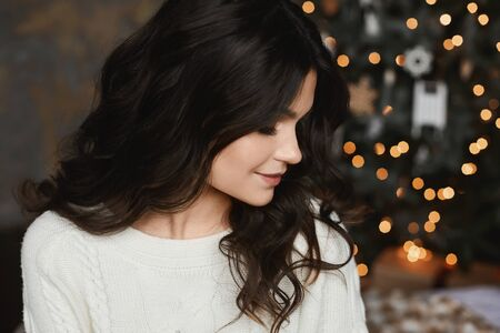 Close up portrait of brunette model girl posing in an interior with festive Christmas lights on the background. Young beautiful smiling woman with a trendy makeup and smooth skin looking aside