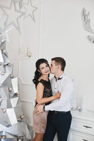 Beautiful couple in love hugging and kissing in Christmas interior. Young brunette woman in skirt and blouse hugging with handsome businessman in a white shirt. Loving married couple. New year