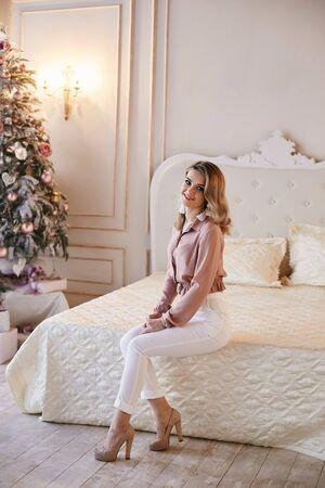 Happy and fashionable model girl with platinum blond hair in a pink blouse and white pants sits on the bed near the Christmas tree. Pretty young woman posing in New years interior Zdjęcie Seryjne