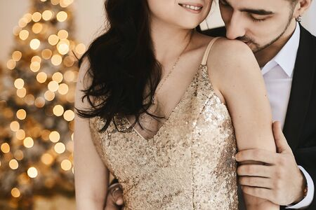 Sexy passionate couple celebrating Christmas together. Attractive woman in gold evening dress and handsome bearded man in a suit posing in an interior with New year festive lights on the background.