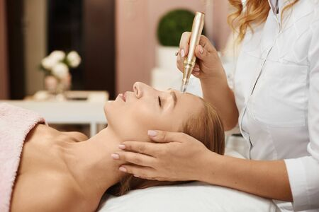 Beautiful woman getting face peeling procedure in a beauty clinic, close-up portrait. Girl with perfect face skin on a non-surgical facelifting procedure. Rejuvenating facial treatment. Stock Photo