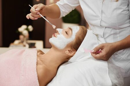 Young beautiful woman during spa, while hands of female cosmetologist applying peel mask to her face with a wide brush. Model girl with scrub on her face. Concept of beauty procedure. Spa therapy.