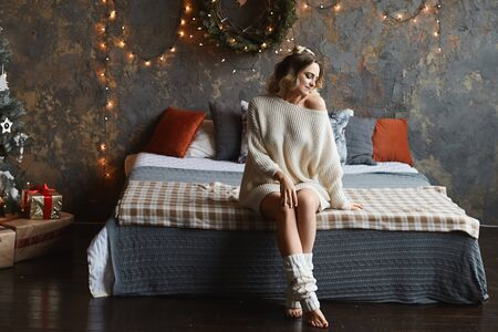 Young woman in cozy home clothes posing on the bed in loft interior near the Christmas tree. Beautiful model girl in a cozy sweater on the bed in the interior decorated for New Year