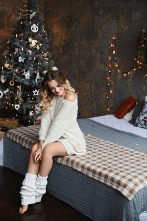 Beautiful model girl with perfect body in a cozy sweater sits on the bed in the interior decorated for New Year. Young woman in modish cozy outfit posing on the bed against Christmas tree in the loft Zdjęcie Seryjne