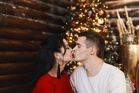 Beautiful young couple, boyfriend wearing sweater and girlfriend in sexy dress kissing in Christmas interior. Young woman in red dress and handsome man hugging and kissing in New years interior