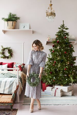 Beautiful and fashionable blonde model girl with Christmas wreath in her hands posing in a bedroom decorated for New year. Young woman in trendy dress in Christmas interior. Concept of Christmas eve