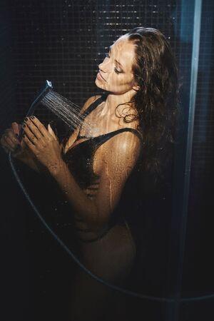 Seductora chica modelo morena con un cuerpo perfecto en bikini negro de pie en la ducha bajo los chorros de agua. Sexy mujer atractiva en traje de baño de moda toma una ducha en un baño oscuro. Foto de archivo