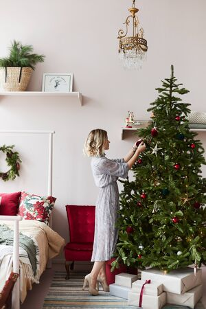 Beautiful and fashionable blonde model girl in trendy dress decorates Christmas tree in a bedroom. Young woman in modish outfit makes decoration in the interior for New year. Concept of Christmas eve Zdjęcie Seryjne