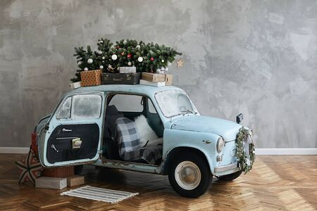 Christmas decorated classic car. A vintage car decorated for New year holidays loaded with festive gifts. Christmas retro car decorated loaded with Christmas tree and presents.