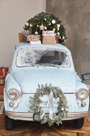 Voiture classique décorée de Noël. Une voiture d'époque décorée pour les fêtes de fin d'année chargée de cadeaux festifs. Voiture rétro de Noël décorée chargée d'arbre de Noël et de cadeaux Banque d'images