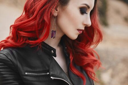 Fashionable close-up portrait of a model girl with red hair and trendy makeup in a leather jacket. Cropped portrait of a young modish woman with red lips and modern trendy hairstyle 免版税图像