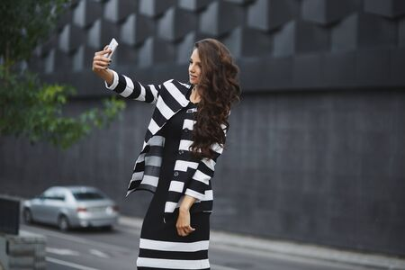 An elegant young woman in a black and white dress taking a selfie with a cellphone in spring day. Beautiful young girl in a trendy dress and jacket on the urban background makes a selfie on the phone 免版税图像